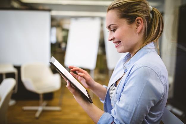 Bizneswoman używa cyfrową pastylkę w pokoju konferencyjnym