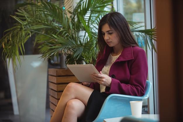 Bizneswoman używa cyfrowego pastylkę w café