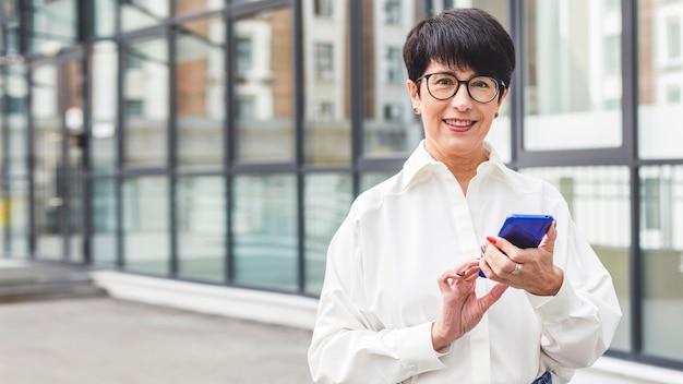 Bizneswoman używa jej przestrzeni kopii telefonu komórkowego