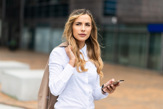 Bizneswoman używa jej telefonu komórkowego na zewnątrz