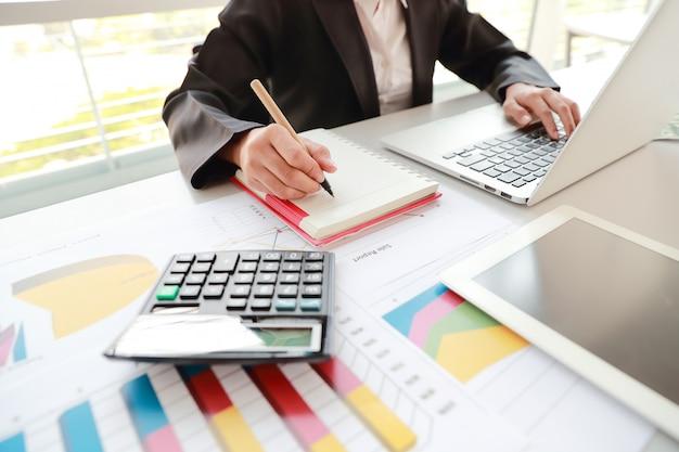 Bizneswoman używa komputer, pastylkę i działanie z wykres firmy raportem podsumowującym