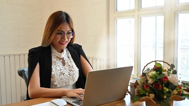 Bizneswoman używa laptop na drewno stole.