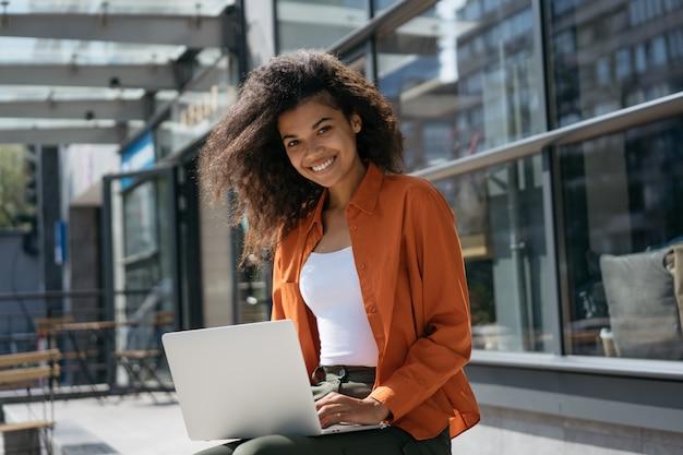 Bizneswoman używa laptop, pisać na maszynie na klawiaturze. udany biznes. uśmiechnięty kobiety copywriter pracuje niezależnego projekt outdoors