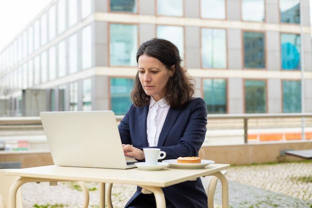 Bizneswoman używa laptop w plenerowej kawiarni