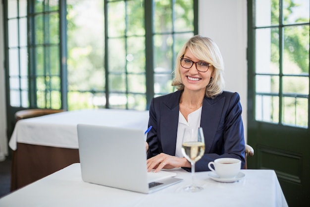 Bizneswoman używa laptop w restauraci