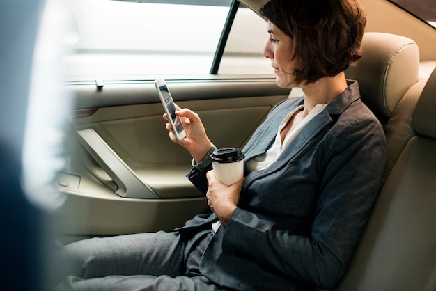 Bizneswoman używa mądrze telefonu samochód inside