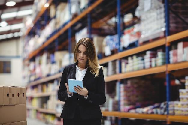 Bizneswoman używa pastylkę w magazynie