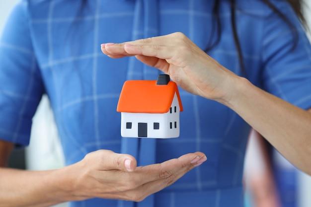 Bizneswoman używa rąk do ochrony koncepcji ochrony nieruchomości w domu