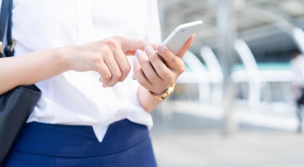 Bizneswoman używa smartphone dla pracującego outside