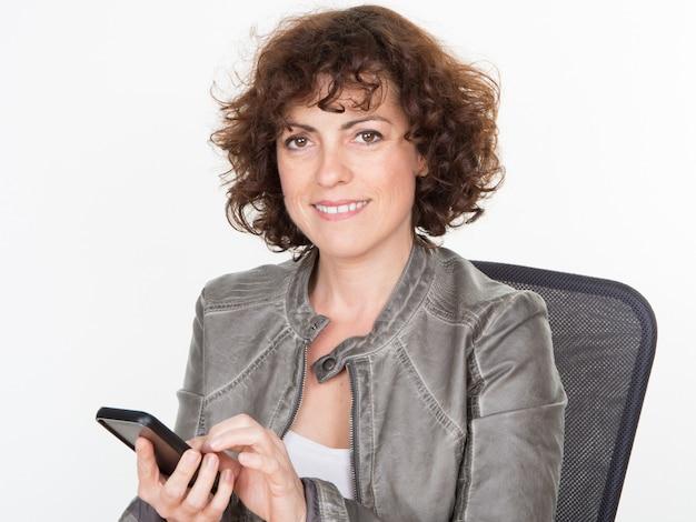 Bizneswoman używa smartphone na biurowego biurka miejscu pracy