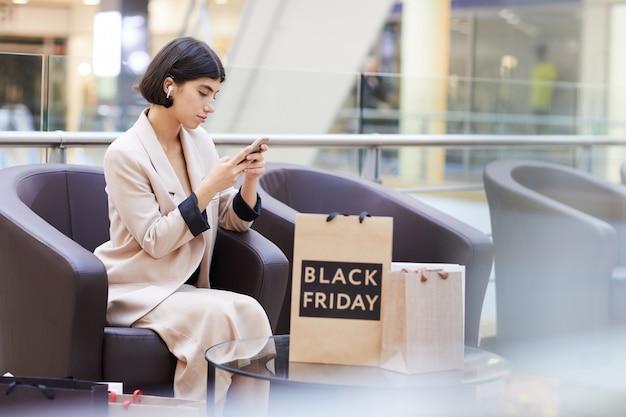 Bizneswoman używa smartphone podczas gdy relaksujący w zakupy centrum handlowym