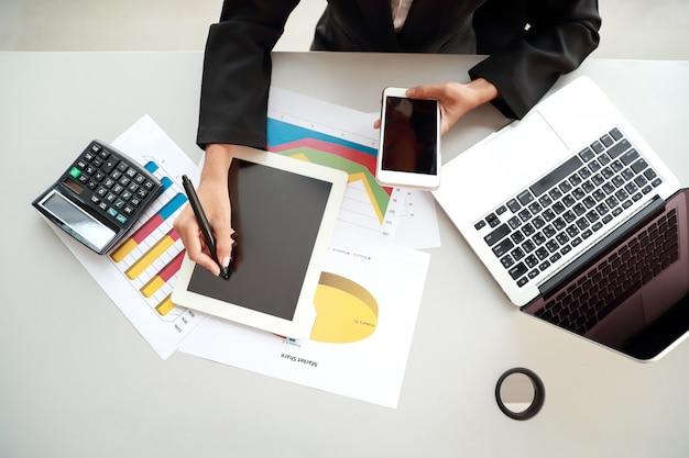 Bizneswoman używa telefon komórkowego i komputer podczas gdy pracujący na firmy zbiorczym raporcie z wykresem