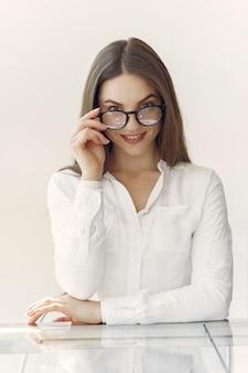 Bizneswoman w białej koszuli siedzi w biurze