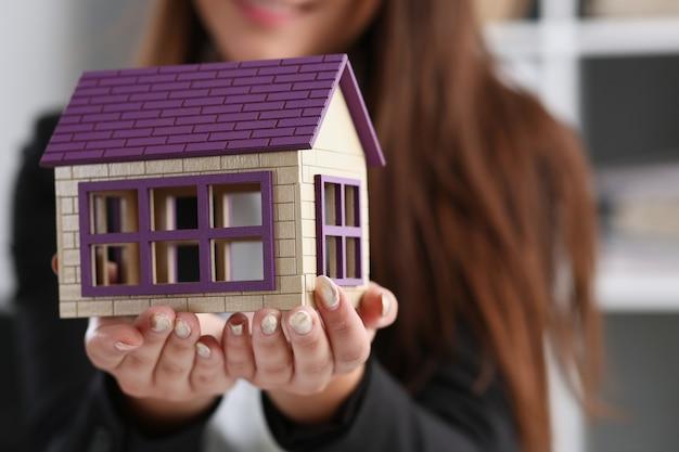 Bizneswoman w biurze trzyma w ręce miniaturowy dom z zabawkami
