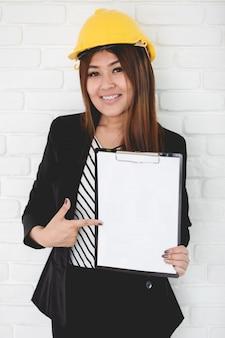 Bizneswoman w biurze z ciężkim kapeluszem i schowkiem