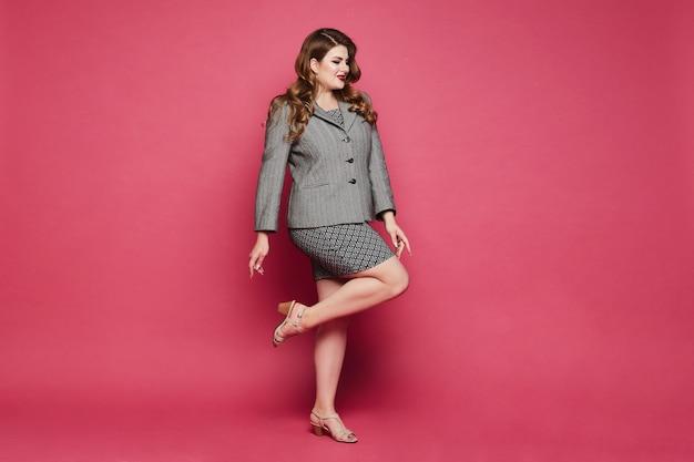 Bizneswoman w dużych rozmiarach w spódnicy z geometrycznymi wzorami iw kurtce pozującej na całej długości