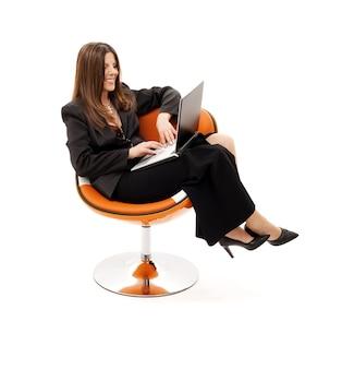 Bizneswoman w fotelu z laptopem nad białym