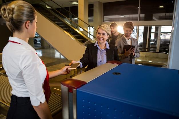Bizneswoman w kolejce otrzymywa paszport i kartę pokładową