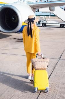 Bizneswoman w kolorze żółtym zostaje blisko lotniczego samolotu