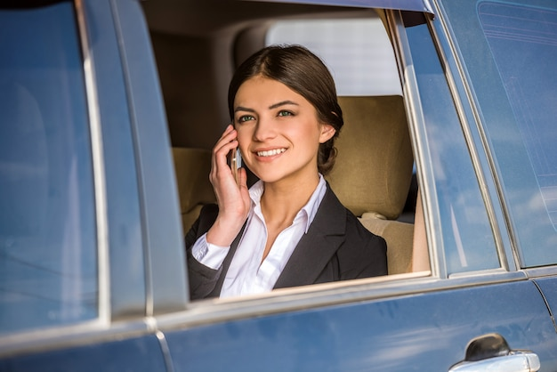 Bizneswoman w kostiumu obsiadaniu w jej luksusowym.