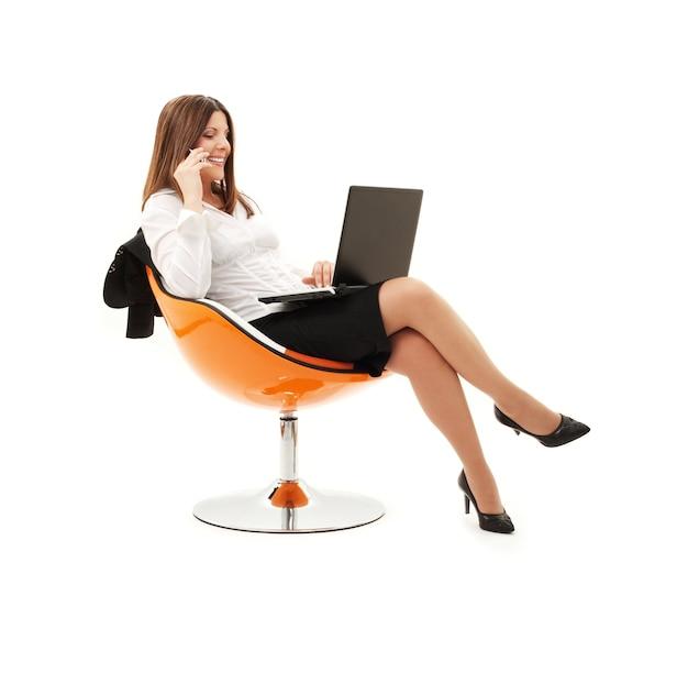 Bizneswoman w krześle z laptopem i telefonem nad bielem