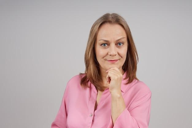 Bizneswoman w różowej bluzce, uśmiechając się i patrząc w kamerę