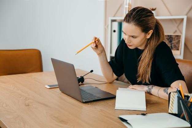 Bizneswoman w słuchawkach siedzi przy biurku, patrzy na ekran laptopa, robiąc notatki