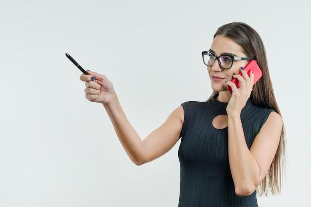 Bizneswoman w szkłach z telefonami wskazuje z piórem