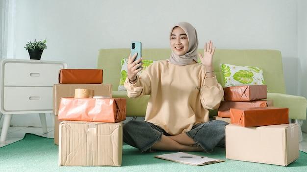 Bizneswoman wita się na ekranie telefonu komórkowego