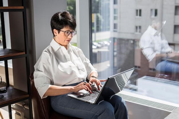 Bizneswoman wpisując na jej laptopie