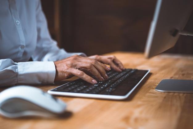Bizneswoman wpisując na klawiaturze komputera