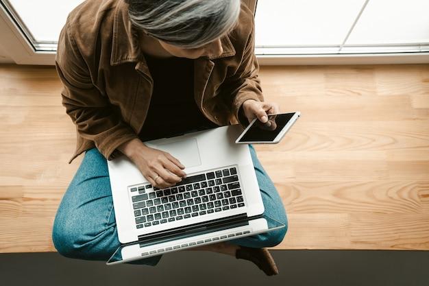 Bizneswoman wpisując na klawiaturze laptopa