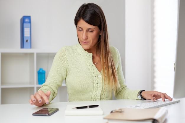 Bizneswoman wpisując na smartfonie w domowym biurze