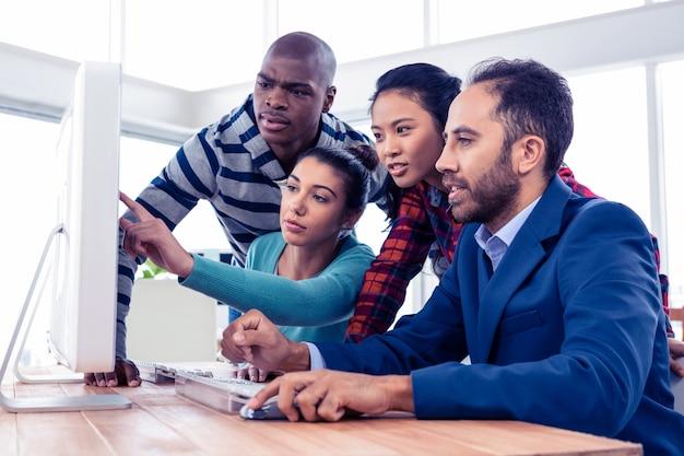 Bizneswoman wyjaśnia kolegów nad komputerem w kreatywnie biurze