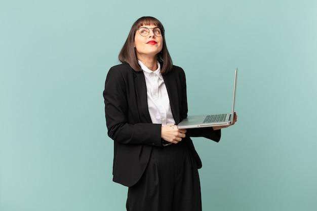 Bizneswoman wzrusza ramionami, czuje się zdezorientowana i niepewna, wątpiąca ze skrzyżowanymi rękami i zdziwiona