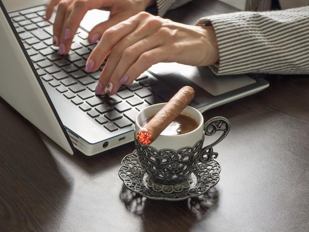 Bizneswoman z cygarem pisze na klawiaturze laptopu