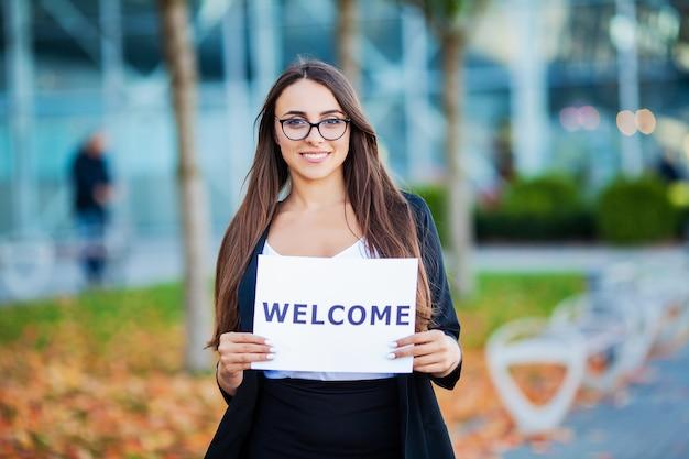 Bizneswoman z długim włosy trzymający szyldową deskę z powitaniem ma lotniskowego tło