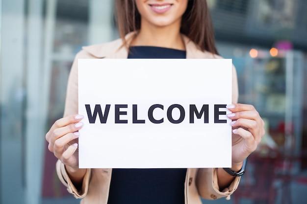 Bizneswoman z długimi włosami trzyma szyldową deskę z powitaniem ma lotnisko