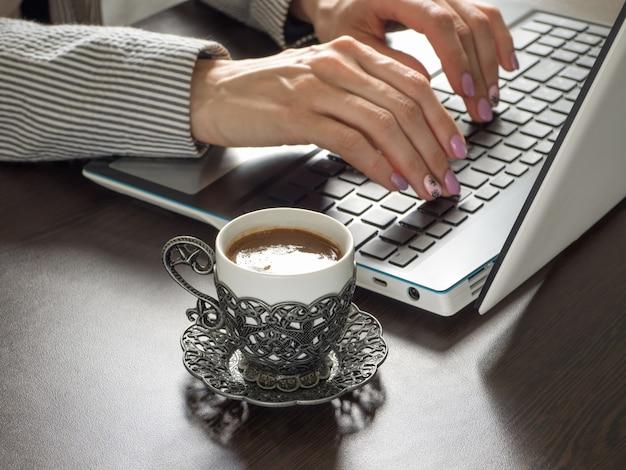 Bizneswoman z filiżanką kawy pisze na klawiaturze laptopa