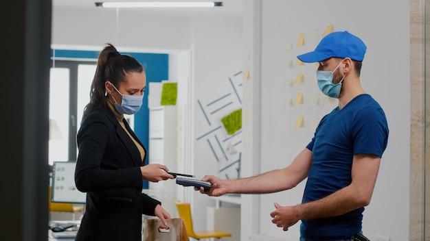 Bizneswoman z maską na twarz odbiera zamówienie na lunch na wynos, płacąc smartfonem za pomocą usługi zbliżeniowej pos