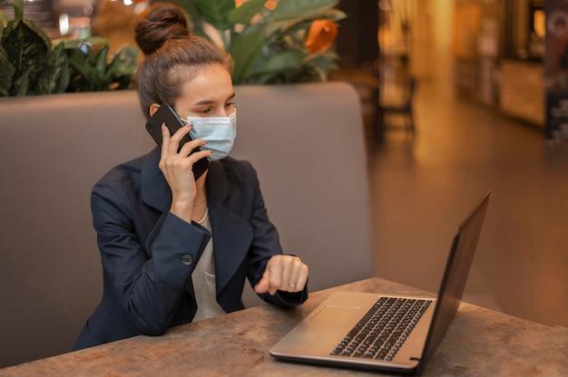Bizneswoman z medyczną maską pracuje na laptopie