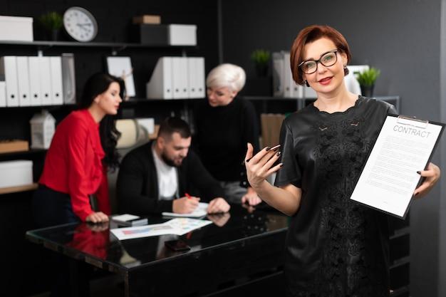 Bizneswoman z piórem i kontrakt na pracownikach biurowych dyskutuje projekt