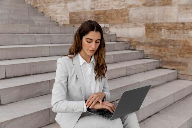 Bizneswoman z smartwatch pracuje na laptopie siedząc na schodach