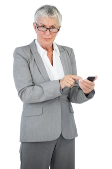 Bizneswoman z szkłami używać jej telefon komórkowego