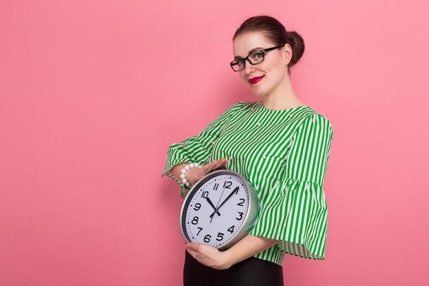 Bizneswoman z włosianą babeczką i zegarami
