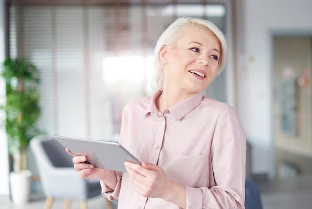 Bizneswoman ze śmiejącym się cyfrowym tabletem
