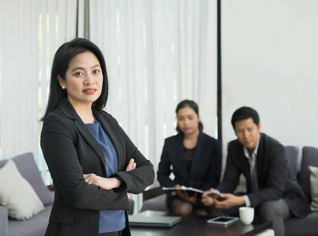 Bizneswoman żeńska lider pozycja i krzyż ręka z drużyną w korporacyjnym spotkaniu