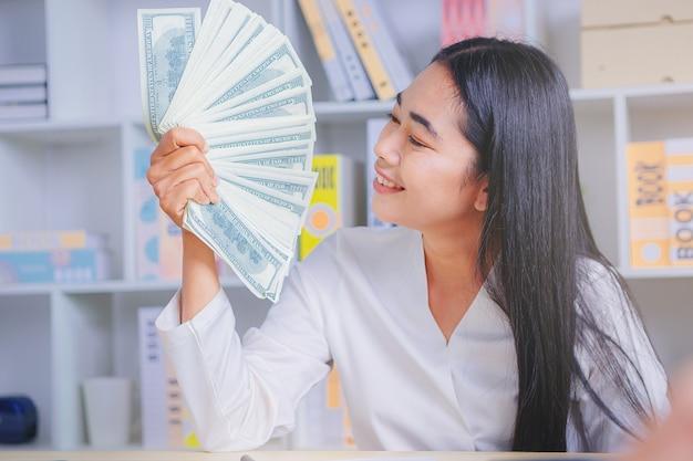 Bizneswoman zwycięzcy szczęścia trzymającego pieniądze z marketingu internetowego wybrane tematy