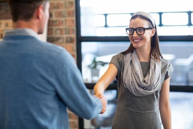 Bizneswomanu chwiania ręki z kolegą w biurze