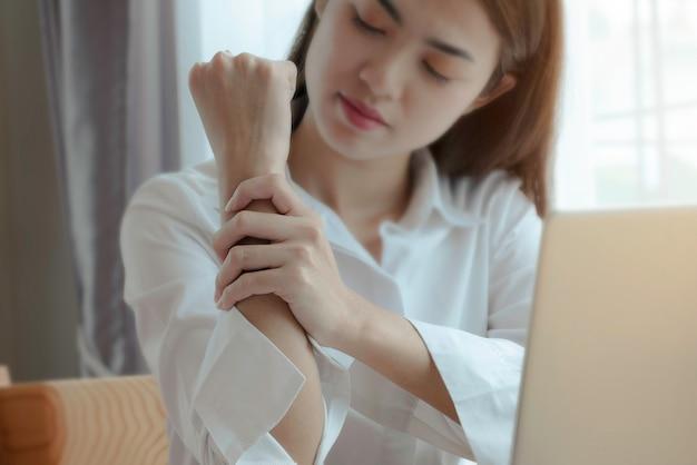 Bizneswomanu cierpienie od nadgarstku boli w biurze podczas gdy woking z laptopem.